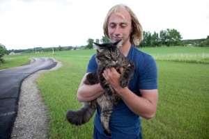 Kevan Yeats is pictured with Momo the cat at his parent's house near Okotoks, Alta. on June 21. Yeats and Momo leapt from Yeats' truck in flowing flood waters in High River, Alberta Thursday. (Jordan Verlage/CP)