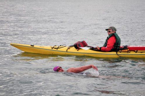 Claudia Rose swims across Kachemak Bay on Aug. 9 as Al Brenner kayaks next to her. Channa Rist via Homer News